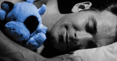 Barbat culcat pe-o parte in timpul somnului